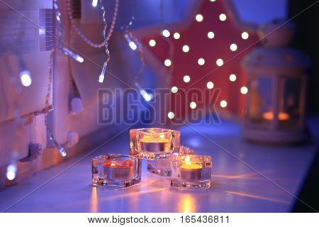 Bright candles and decorative lights at night. Candles on soft focus backdrop.