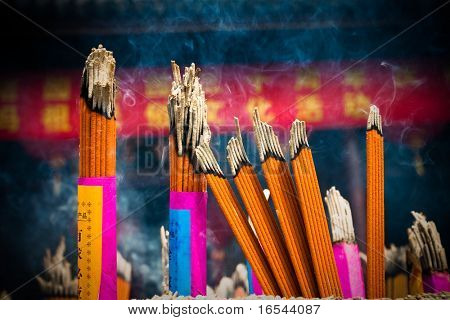 Incense sticks and candles in an Buddhist temple in Bangkok