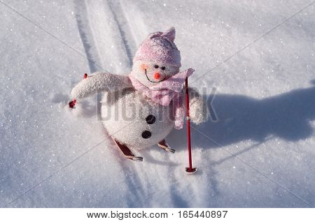 Textile snowman with snow slides down hill skiing clear winter day