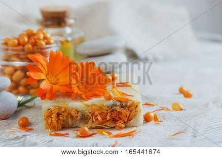 Natural handmade soap with calendula and sea-buckthorn on white wooden background