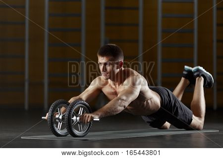 Portrait full length of muscular man doing sport exercise at gym, on floor with toning wheel, abdominal exercise equipment. Wearing black shorts, with bare torso. Looking away. Working on body.