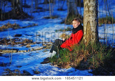 young smiling girl in red coat sitting on the thawed patch with green grass near a tree in the snow in a fabulous wild forest.