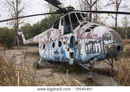 Wreck of an Old Soviet military chopper in a garden outdoor.