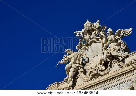 Emblem of Pope Clement XII between angels with trumpets at the top of the beautiful Trevi Fountain in Rome (with copy space)