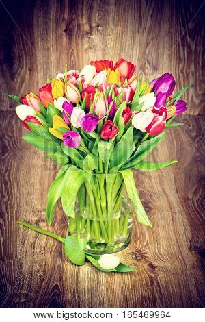 Tulips in the vase on wooden background. Toned image