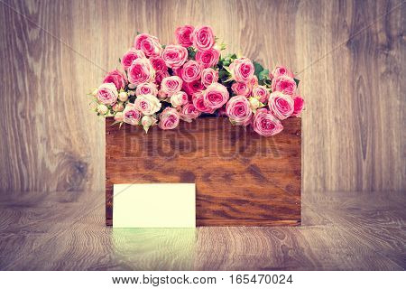 Roses in the box on wooden background. Toned image