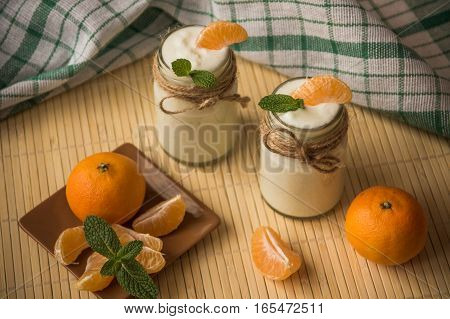 Fresh Organig Natural White Yogurt In Glass Jars With Tangerine And Mint