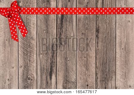 Decorative red ribbon on the old wooden table. Top view.
