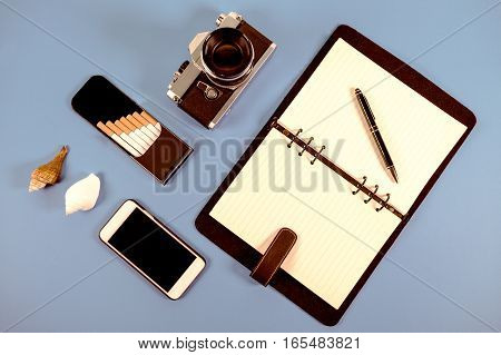 Accessories with blue background notebook and pen camera box of cigarette and mobile phone