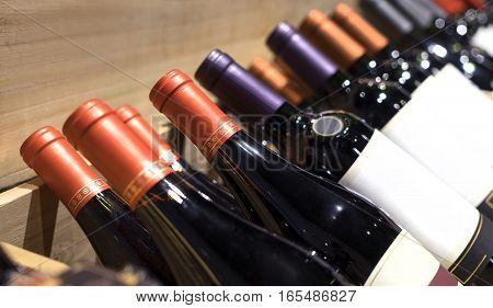 Wine shop. Closeup shot of wineshelf. Bottles lay over straw.