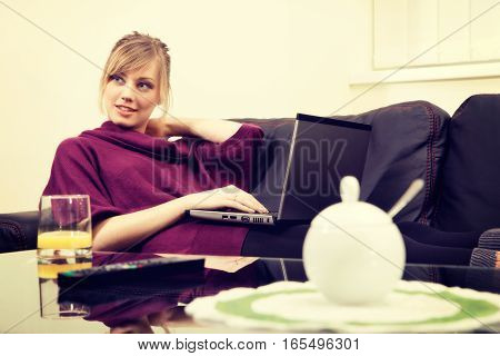 Young Woman With Blond Hair Working On Her Laptop At Home