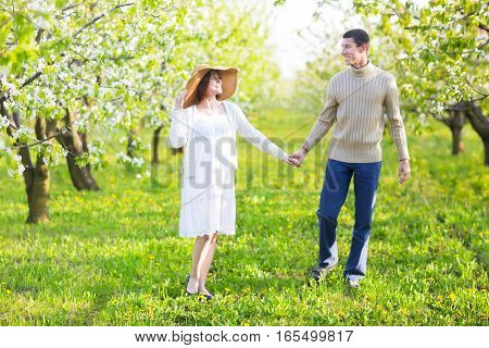 Portrait of a happy pregnant couple in the blossom garden