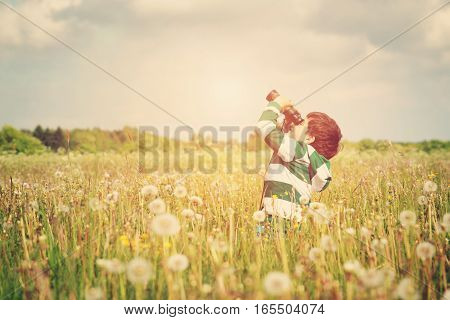 Child watching in benoculars on the field with dandelions. Boy playing on the meadow in summer