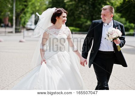 Happy Wedding Couple Walking Holding Hands And Smiling.