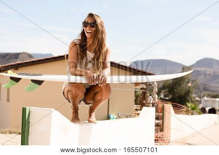 girl squats on wall with a surfboard