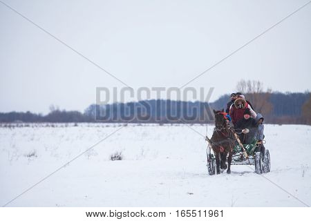 Pietrosani Romania - January 6 2017: People ride a horse drawn cart on a snowy field before a traditional Epiphany horse race in Pietrosani Romania.