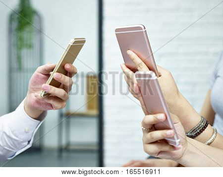 hands of young people sitting together playing with cellphones.