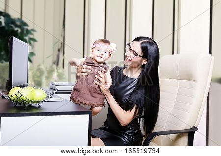 Beautiful young mother with her little cute daughter at the workplace in the office
