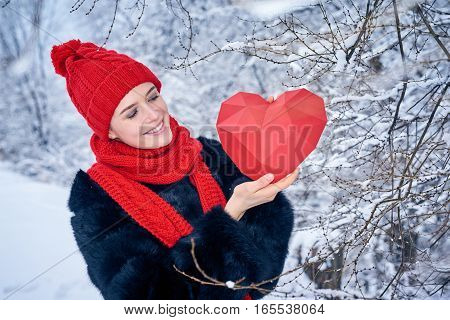 Love and valentines day concept. Portrait of smiling woman holding red polygon paper heart shape over winter landscape