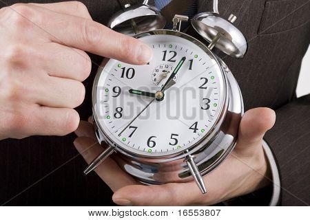 Geschäftsmann auf einem Wecker-Ergebnis nach 9 Uhr