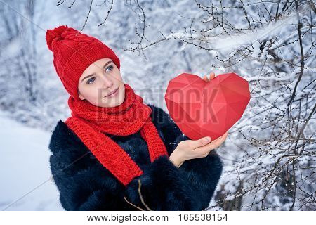 Love and valentines day concept. Pensive smiling woman holding red polygon paper heart shape looking away at copy space, over winter landscape