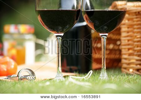 Wine glasses and hamper picnic scene