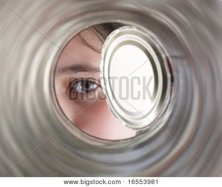 Curious girl peeks into a tin can expecting a big surprise