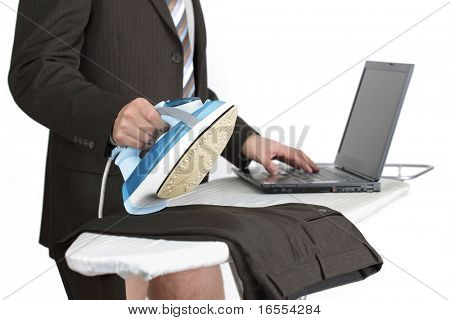 Businessman working from home on laptop computer whilst doing the chores