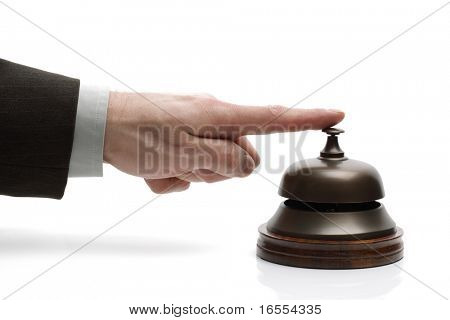 Businessman ringing a hotel reception service bell to request assistance