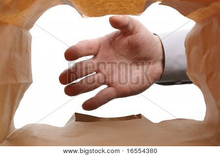 Hand reaching into a paper bag to remove contents
