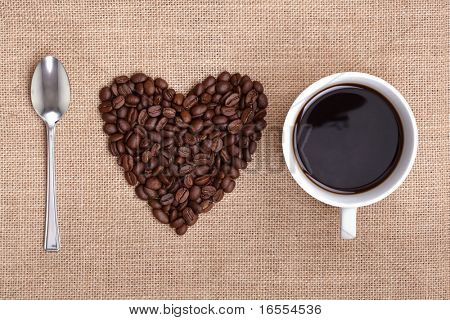 Heart shape made from coffee beans with a spoon and cup of coffee on hessian spelling I love coffee