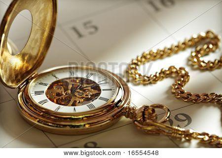 Close up einer gold Taschenuhr in einem Kalender im Sonnenlicht