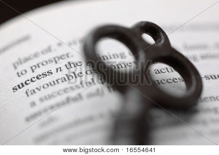 Antique key resting on the dictionary definition of success