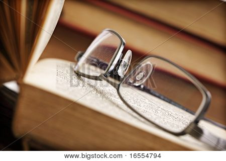 Modern spectacles resting on an open hardback book