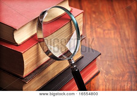 Stack of antique books with magnifying glass on wooden table