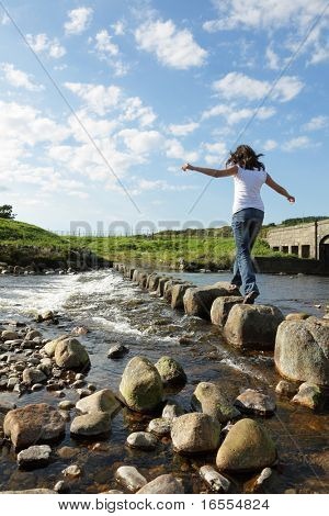 Young girl runs across stepping stones  to cross a stream