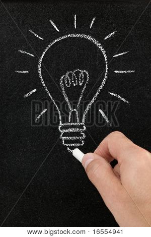 Hand drawing a lightbulb on a chalkboard symbolizing ideas, inspiration and creativity