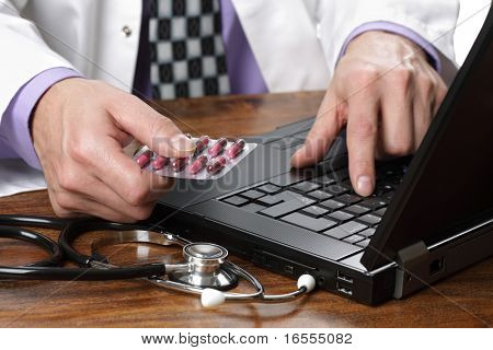 Doctor using a laptop computer to prepare an online prescription or writing patient notes from a medical examination