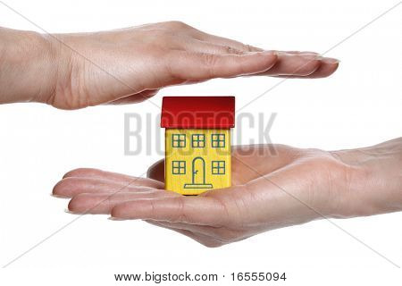 Female hand protecting a model house, real estate or insurance concept