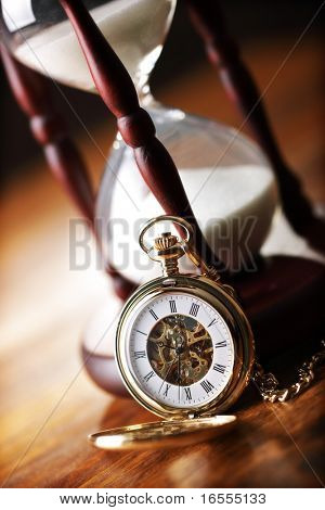Hour glass or sand timer with vintage pocket watch, symbols of time