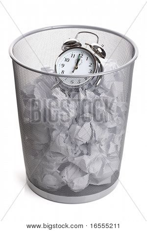 Alarm clock in a wastepaper bin concept for a time waste of time