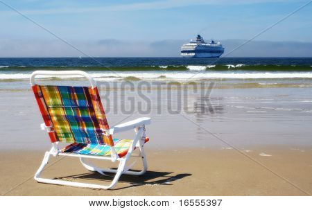 Empty chair on a beach with ocean and cruise ship in background