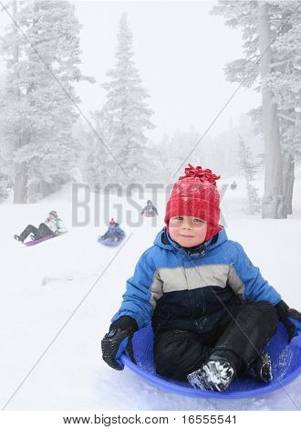 Four year old boy sledding in snowy landscape