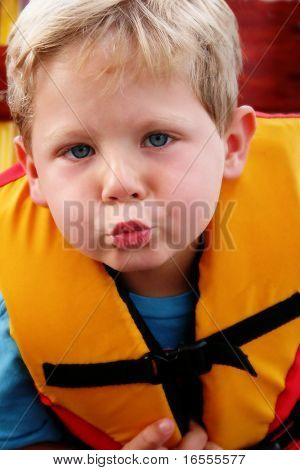 Happy four year old boy wearing a life jacket