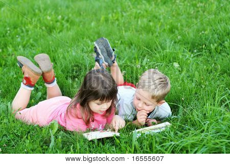 Kids reading a book on grass