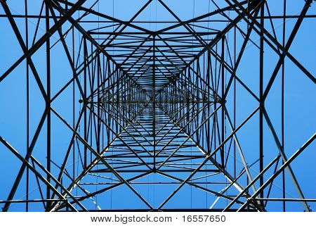 Steel electricity pylon on bright blue sky