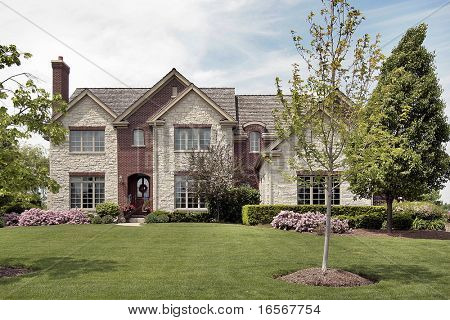 Front view of stone and brick home in spring