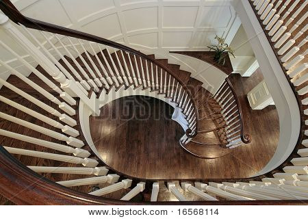 Spiral staircase in luxury home with wood railing