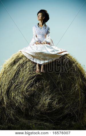 Beautiful woman in vintage dress sitting on haystack