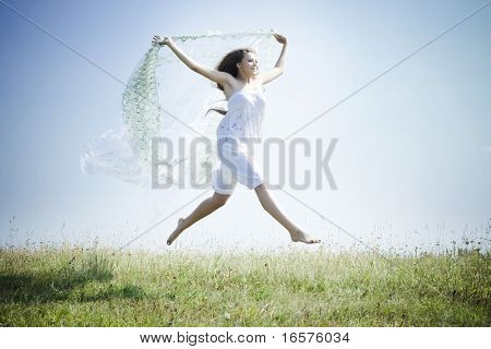Woman  jumping with a white scarf on the meadow